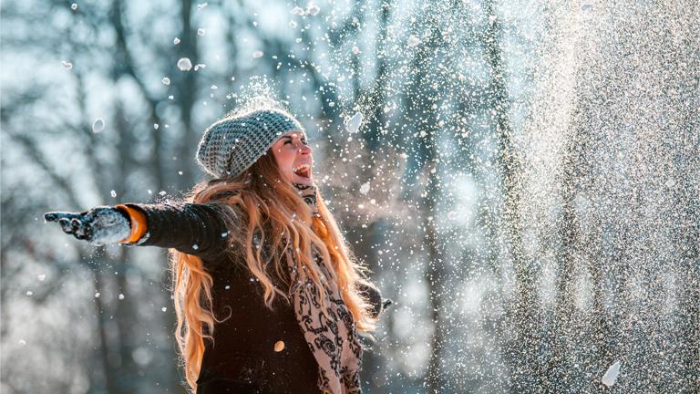 glückliche Frau im Winter Immunabwehr schnee werfen