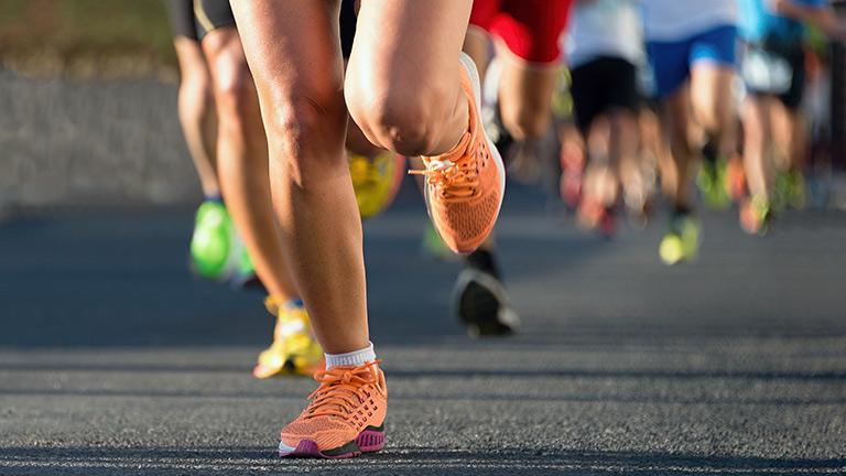 Laufen regelmäßig Immunsystem stärken Sport Beine Sportschuhe orange
